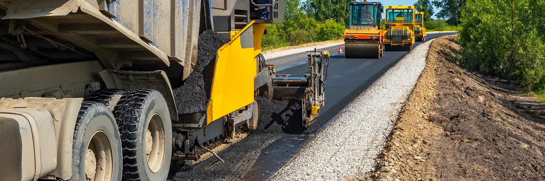 A yellow dump truck pours asphalt for a roller truck paving the road.