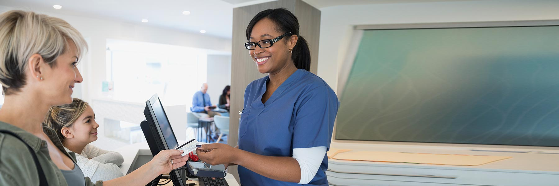 Healthcare practitioner in blue scrubs and black glasses at computer accepting credit card for payment from customer