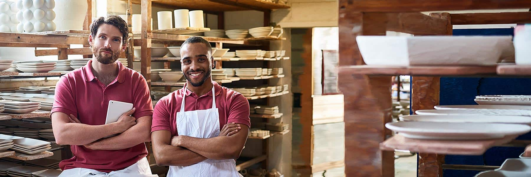 Two restaurant business partners in red shirts and white aprons smiling with folded arms in front of shelves of dishes