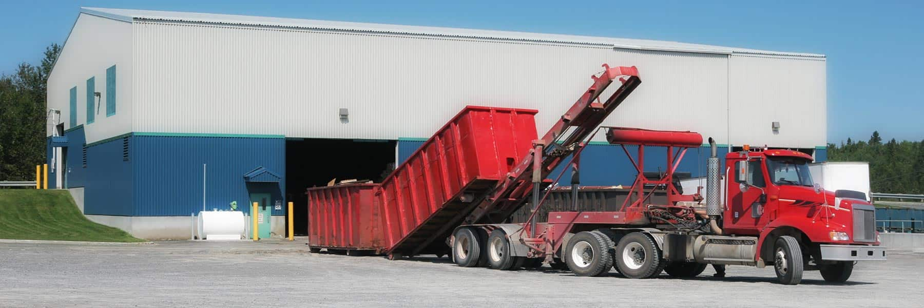 A tractor trailer unloads a delivery of large red recycling or garbage bins to a plant.