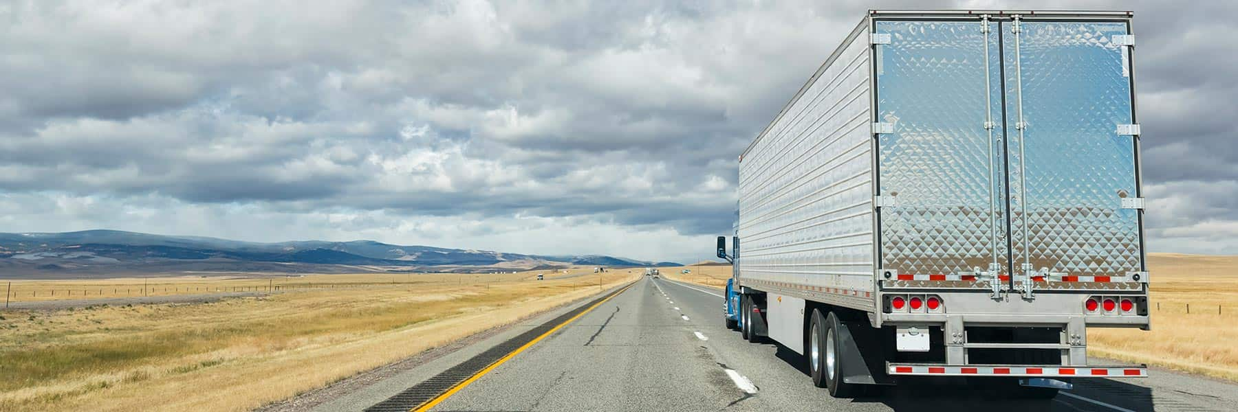A shiny silver tractor trailer drives on an empty road into the distance toward the mountains under partly cloudy blue skies.