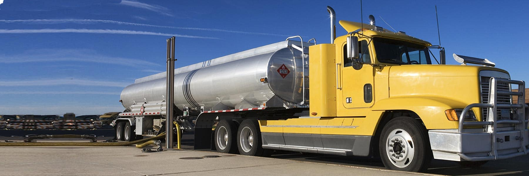 Large bright yellow gas tanker truck parked for filling up on bright sunny day with deep blue sky