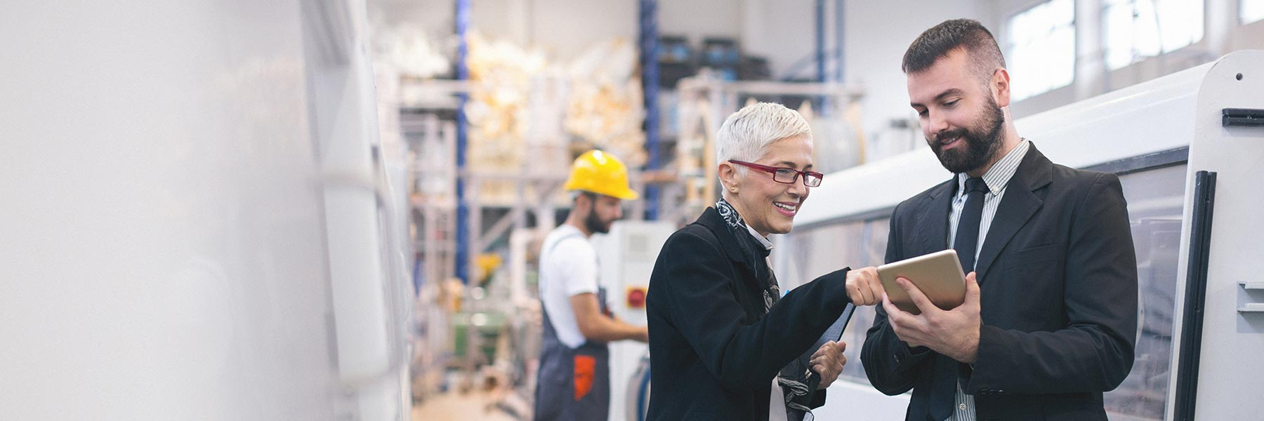 A business woman with white hair and red glasses smiles and points to a tablet held by a business man with a beard, as they stand in a factory surrounded my technology machinery.