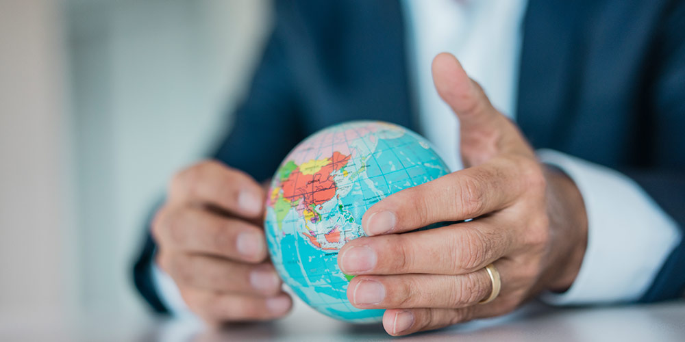 Close-up on the hands of a business man who is wearing a navy jacket and white shirtgold band, sitting at desk with a miniature globe
