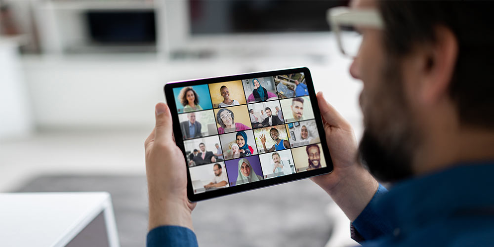 A business man in glasses and a blue shirt holds a tablet showing a video call with several other people.