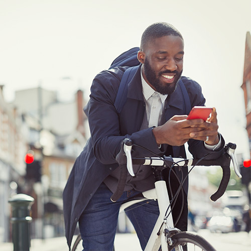 Younger business man with beard wearing dark blue coat and backpack checking mobile phone while stopped on bicycle