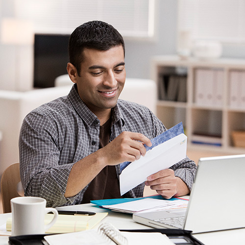 Man with dark hair in unbuttoned shirt sits with white coffee mug and open laptop opening envelope from stack of mail
