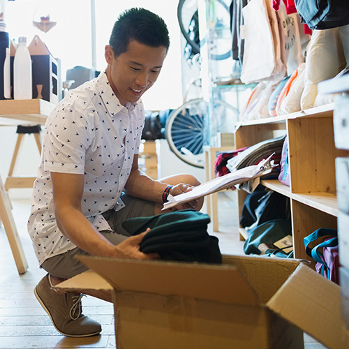 Small business owner with clipboard kneeling in front of wooden wall shelves unpacking box of inventory inside retail shop