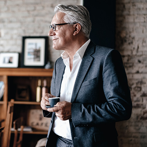 Business man with white hair in gray jacket, white shirt and glasses stands holding small coffee cup smiling