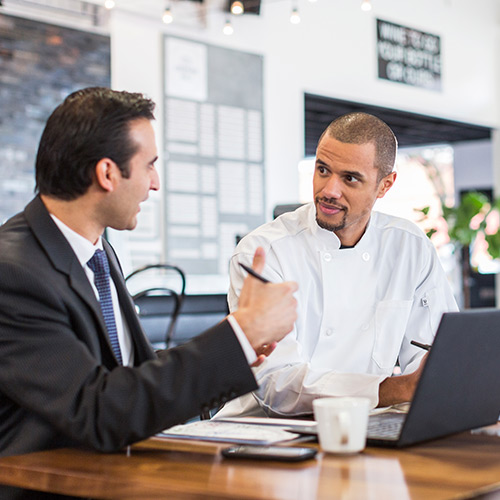 Chef listening to dark-haired business man in suit with open laptop and coffee sitting at wooden table in restaurant