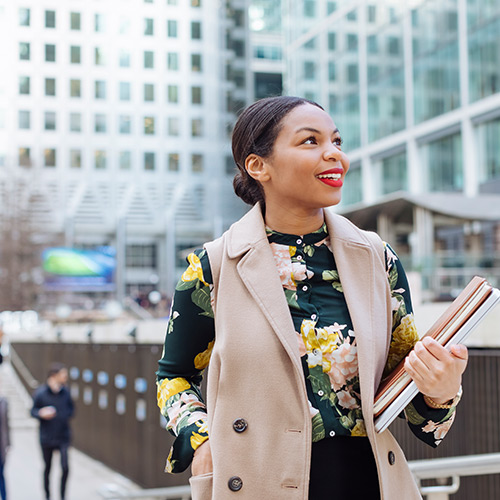 Woman walking in city wearing floral top with khaki vest and hair pulled back smiles while looking up and carrying books