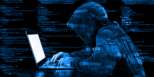 Dark dramatization of hooded cyber hacker sitting hunched over in front of glowing laptop screen typing