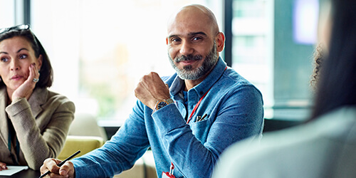 Bald business man with beard in blue shirt sitting and red lanyard sitting listening at meeting table holding pen