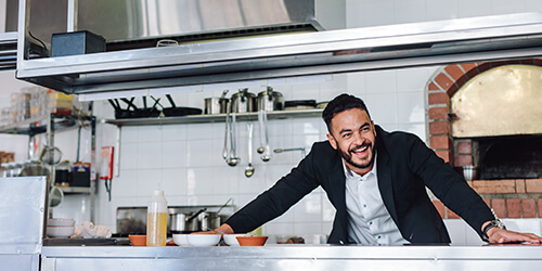 Delighted restaurant franchise owner standing with outstretched arms on counter of commercial kitchen with big wide grin