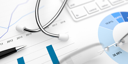 Closeup of a stethoscope, pen, glasses and keyboard on top of healthcare finance reports.