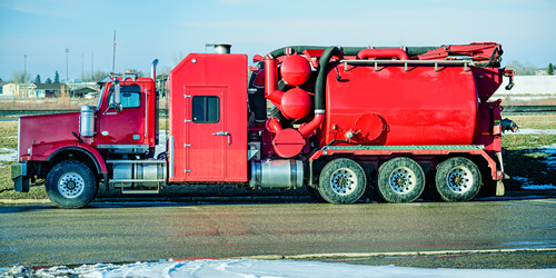 A red hydro vac excavator truck sits on the side of the road next to melting snow on the grass.