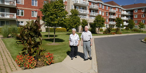A senior couple takes a walk on a warm summer day on the sidewalk around their retirement home