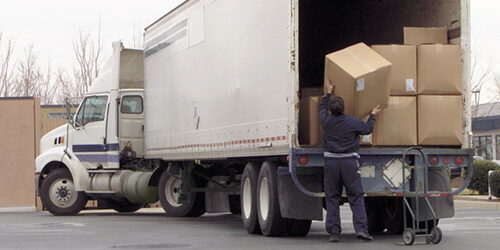 Transportation worker in dark blue jacket and pants unloads large boxes from back of parked white semi trailer truck