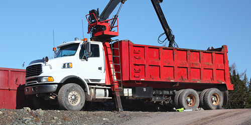 White and red dump truck with black scoop shovel and ladder parked on gravel construction site on sunny blue sky day