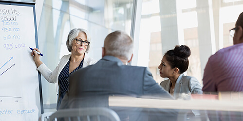 Mature business woman in black glasses writing on board while standing during group meeting