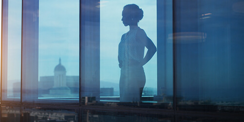 A business woman with her hands on her hips stands in her office window and looks out at the city buildings