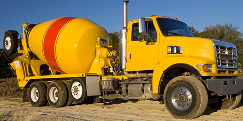 A yellow cement mixer truck with a large orange stripe is seen on a road.