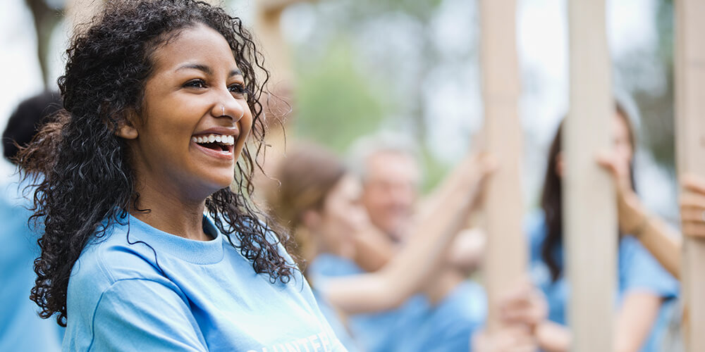 Young woman with long brown curly hair wearing light blue volunteer t-shirt standing smiling with arms folded