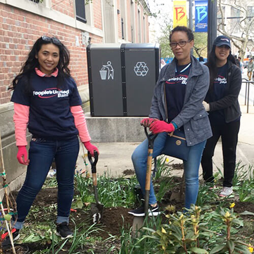 Three People's United Bank employee volunteers in navy blue t-shirts standing with shovels outside working on city garden