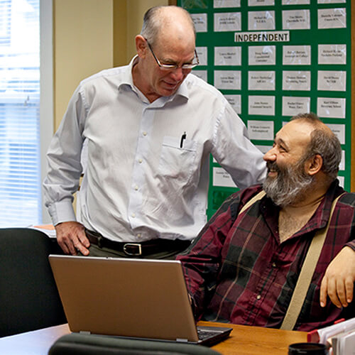 Older man with glasses in button-up standing beside bearded man in plaid shirtsuspenders seated at desk with open laptop