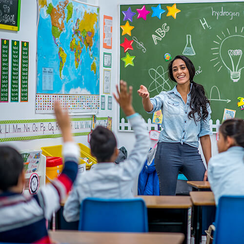 Young teacher with long dark ponytail wearing blue standing in a classroom of kids sitting at desks with raised hands