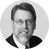 Black and white headshot of male investment professional with brown hair a full beard and glasses on a gray background