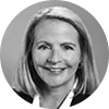 Black and white headshot of smiling female investment professional with shoulder length blond hair on a gray background