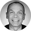 Black and white headshot of smiling male investment professional on a light background