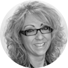 Circular black and white headshot of professional female mortgage officer smiling with curly blonde hair and glasses