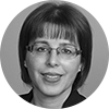 Circular black and white headshot of professional female mortgage officer with short brown hair, bangs and glasses