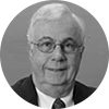 Circular black and white headshot of mature professional male mortgage officer with white hair and glasses