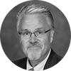 Black and white headshot of mature male financial advisor with white hair, beard and glasses on a gray background