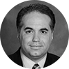 Black and white headshot of male financial advisor with dark brown hair on a gray background