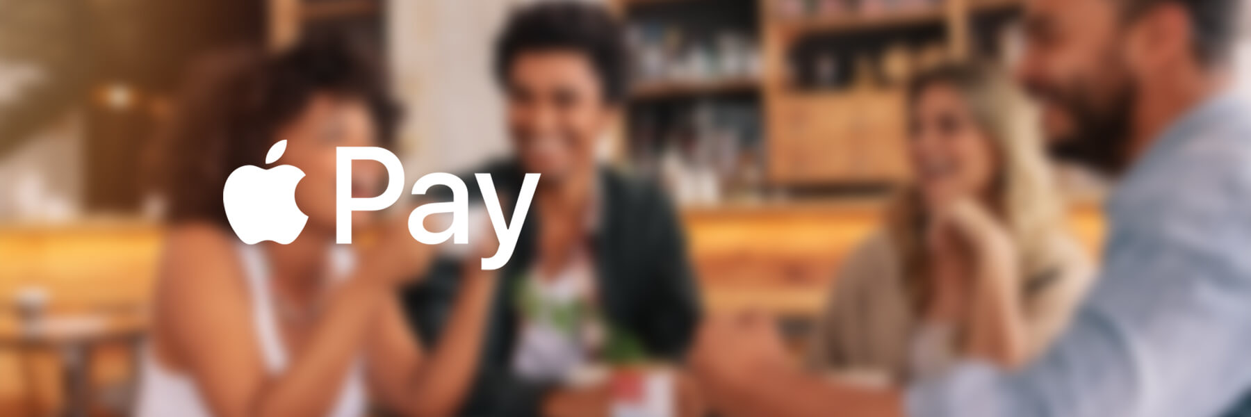 White Apple Pay logo on top of a blurred image of friends laughing together in a coffee shop.
