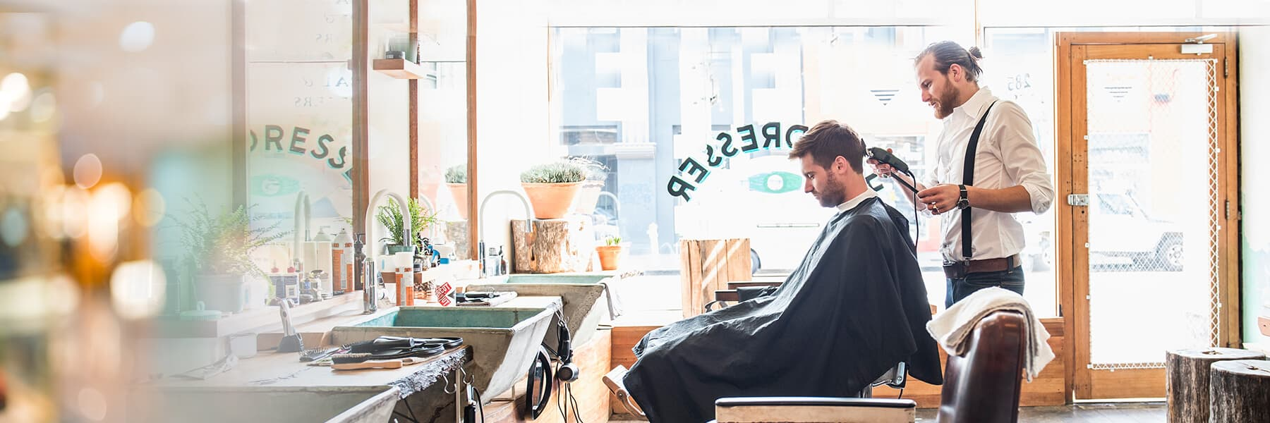 Young man with beard looks down while seated in barber shop chair getting haircut from a young barber in suspenders