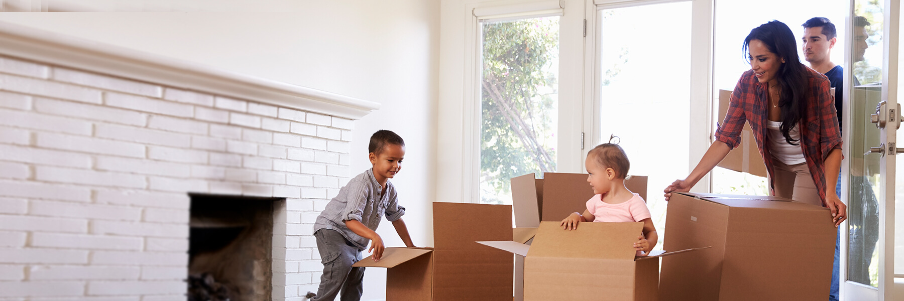 Family with young children moving into their new home unpack boxes in the empty  living room