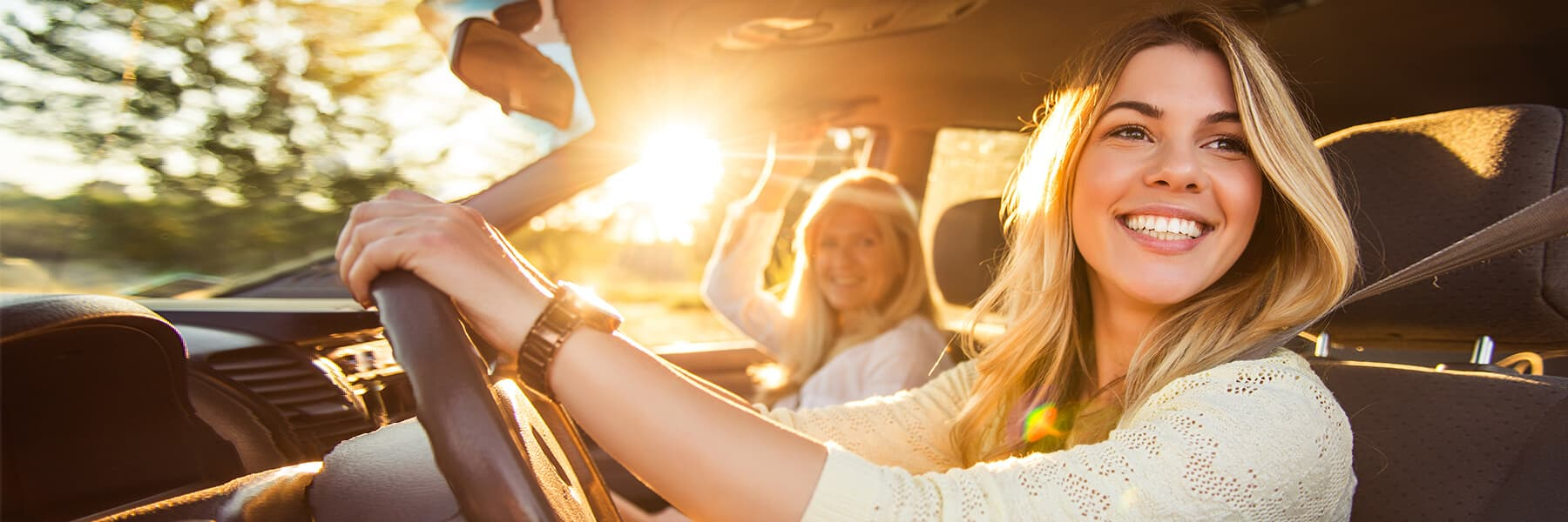 A smiling teenage girl in a white shirt is driving while a woman sits in the passenger seat with a sun glare behind them.