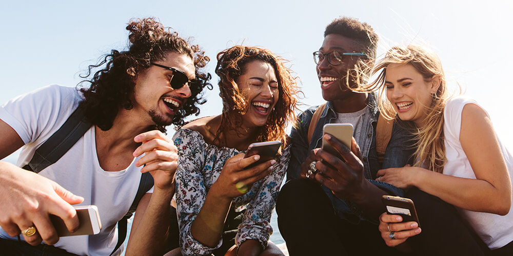 Group of friends holding mobile phones sit outdoors and laugh as one friend shares his phone with the others