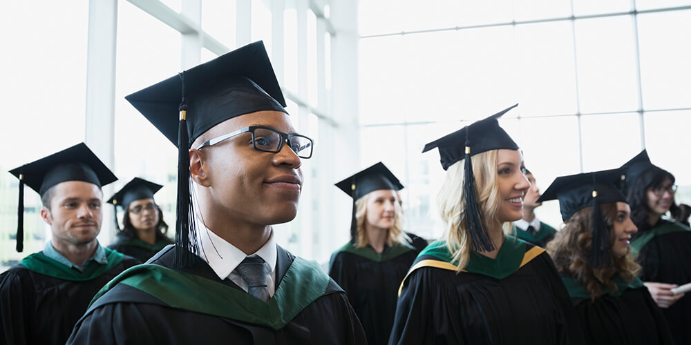 Man in glasses smiles as he listens with other graduating students in their black and green caps and gowns in a sunlit atrium