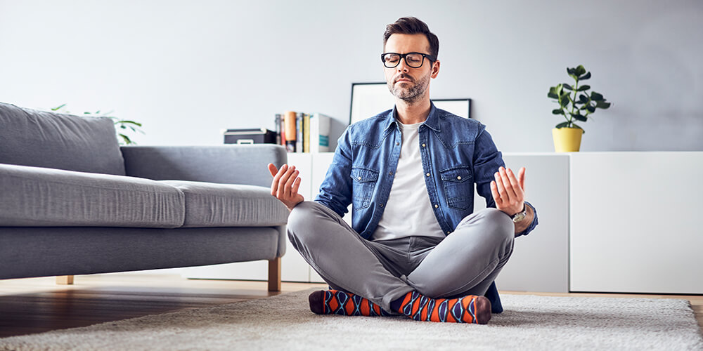 A man in glasses and a blue button down shirt sits cross-legged on his living room floor, hands on his knees facing upward in meditation.