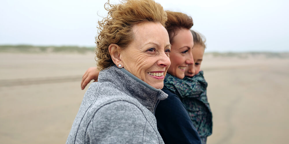 A grandmother, daughter and granddaughter wearing jackets at the beach on a windy, chilly day.