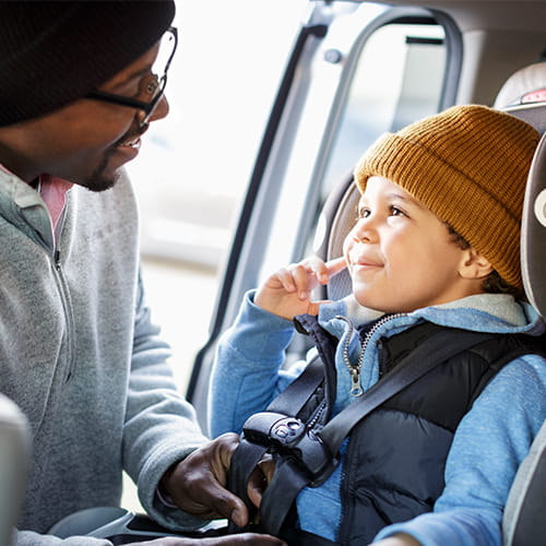 Man in black knit hat straps his young smiling son in brown knit hat into his car seat