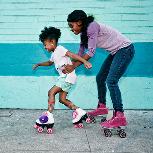 Mother holds onto daughters waist while she learns to roller skate down the sidewalk in front of a blue brick wall