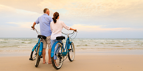 Mature couple with their backs to the camera stands on the beach holding blue bicycles.