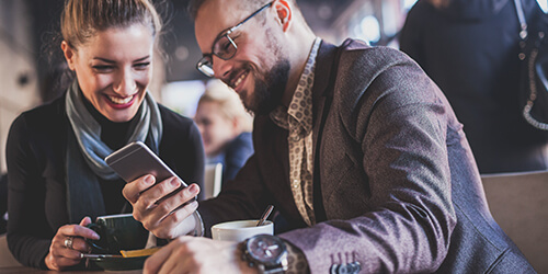 Man in glasses and suit jacket seated next to well-dressed woman sharing mobile phone screen while both enjoy coffee
